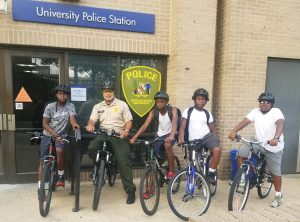 Cpl. Milton Johnson alongside area youth before setting out on an afternoon of biking on and around campus