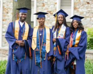 Four Morgan students in their cap and gowns