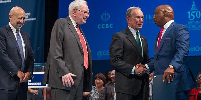 photo of Goldman CEO, Warren Buffett, and Michael Bloomberg congratulating one of the program graduates